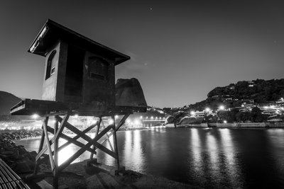 A Battered Hut At The Water's Edge Framed By City Lights
