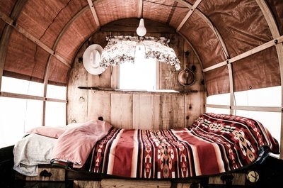 A Bed With A Blanket Inside A Caravan
