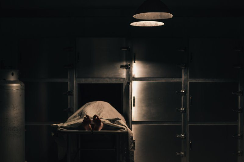 A Body Sits In A Slider Under A Blanket In The Morgue