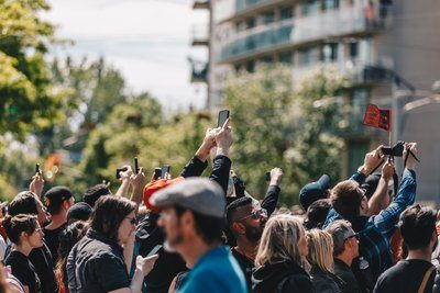 A Crowd Holds Up Their Phones In The Sun