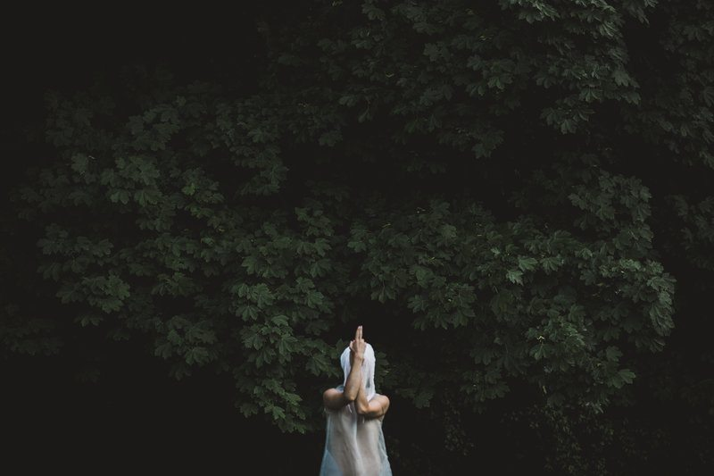 A Figure In White Gauze Strikes A Pose In The Woods