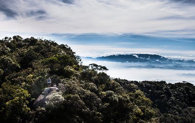 A Hillwalker Crests A Grassy Summit Above The Clouds