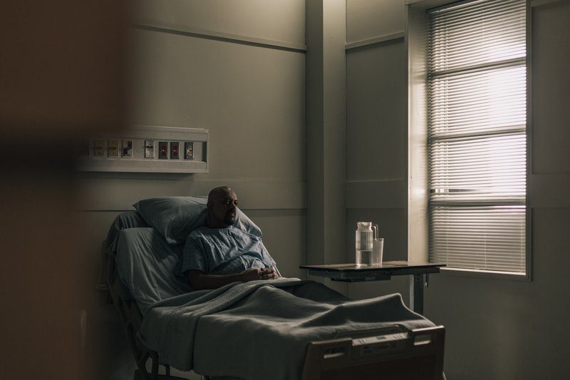 A Hospital Patient Sat In Bed With His Hands Crossed