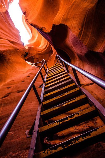 A Ladder Scales The Steep Sides Of A Red Sandstone Cave