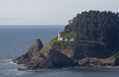 A Lighthouse On A Tree-Covered Peninsula