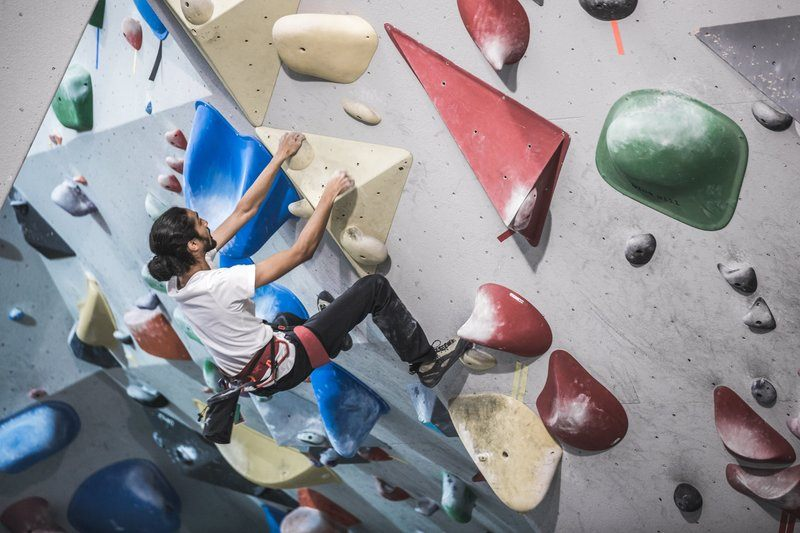 A Man Hangs From The Side Of A Rock Climbing Wall