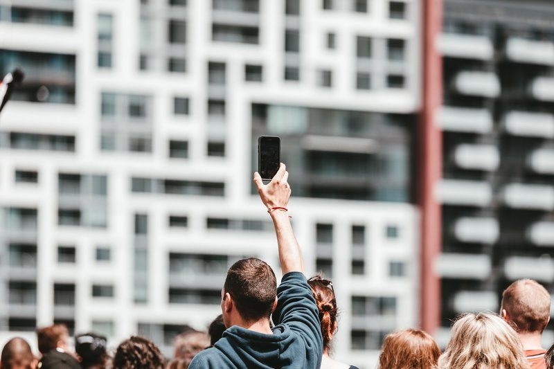 A Man Holds Up A Mobile In A Crowd On A Bright Day