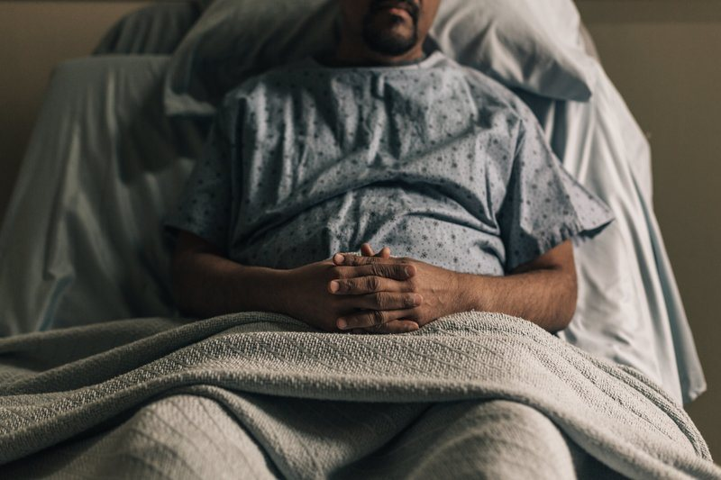 A Man Propped Up In Hospital Bed With Hands Crossed