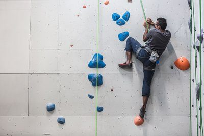 A Man Scales The Side Of A Rock Climbing Wall