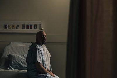 A Man Sits On His Hospital Bed And Stares Into The Distance