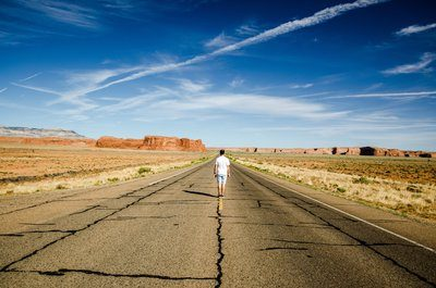 A Man Stands On The Road Markings Of A Desert Highway