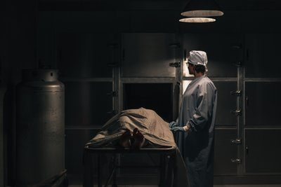 A Mortician Prepares A Body For the Freezer In The Morgue