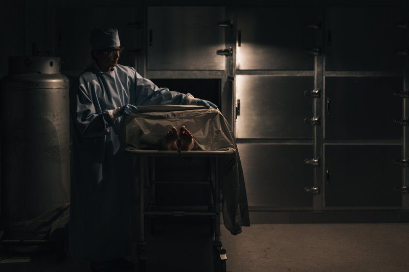 A Mortician Pulls A Blanket Over The Feet Of A Corpse