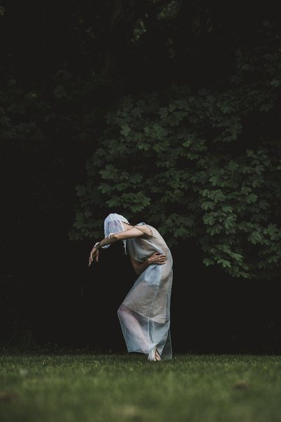 A Person In White Netting Strikes A Pose In The Woods
