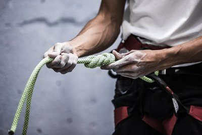A Rock Climber Holds Out Knotted Rope