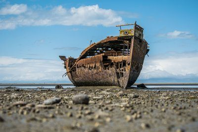 A Rusty Shipwreck Sits On the Shore