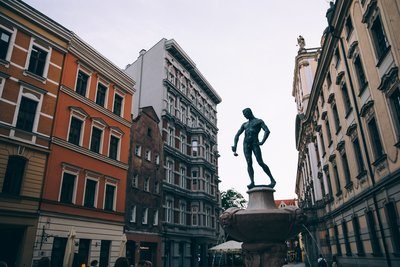 A Statue Of A Man Holding A Ladle In A Town Square