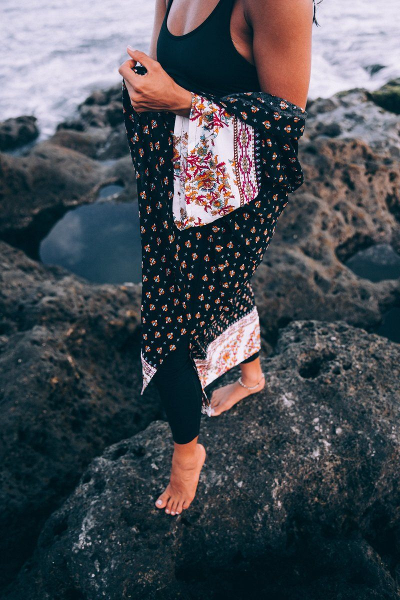 A Tanned Woman With Patterned Shawl Poses On Beach