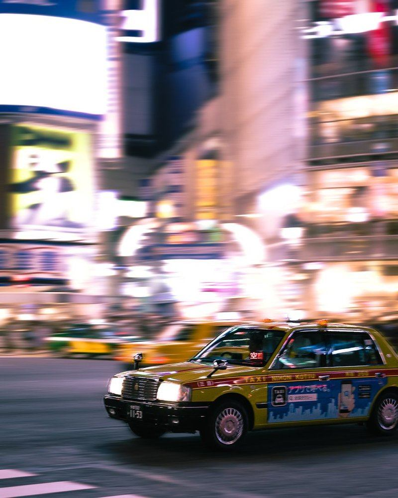 A Taxi In Japan Hurtles Through City Streets