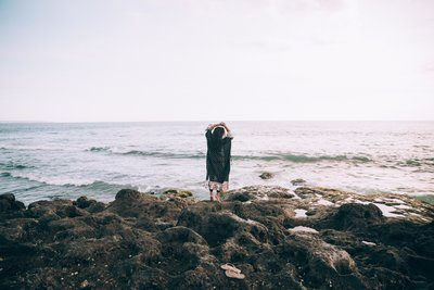 A Woman By The Beach Holds Her Hands Up In Reverie