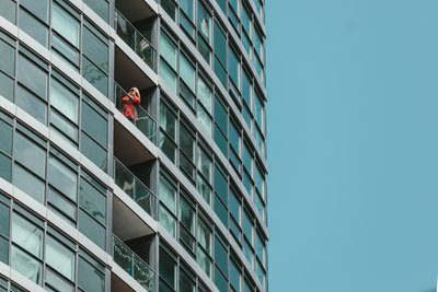 A Woman In A Red Jacket Inspects Her Phone On A Balcony