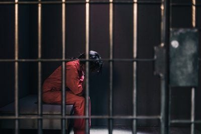A Woman In An Orange Jumpsuit Sits In A Prison Cell