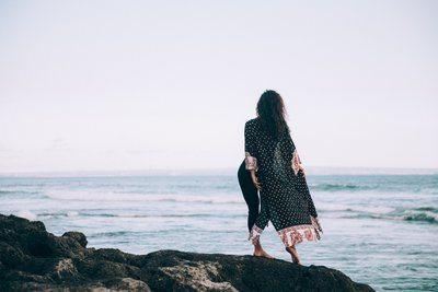 A Woman In Flowing Patterned Robe Stands By Waters Edge