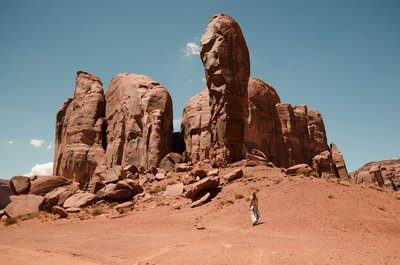 A Woman Looks Up At Stubby Stone Fingers Of Desert Mountains