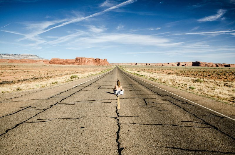 A Woman Sits In The Middle Of A Desert Highway