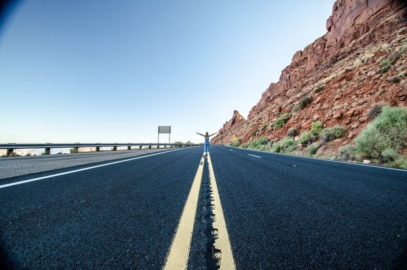 A Woman Stands In The Middle Of A Desert Highway