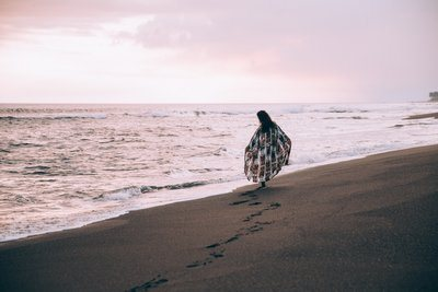 A Woman Walks Along The Beach Leaving Footprints In The Sand