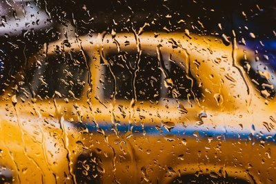 A Yellow Taxi Behind A Rain-Spattered Window