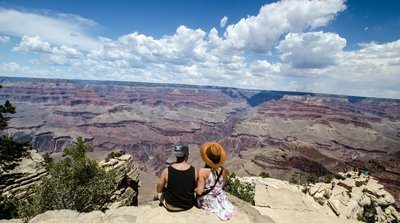 A Young Man And Woman Chat Over A Canyon