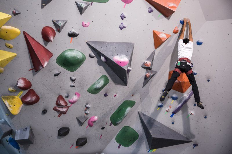 A Young Rock Climber Hangs From A Wall