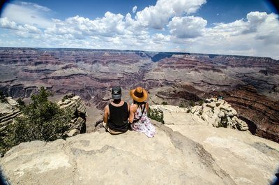 A Young Woman And Man Sit Overlooking A Canyon