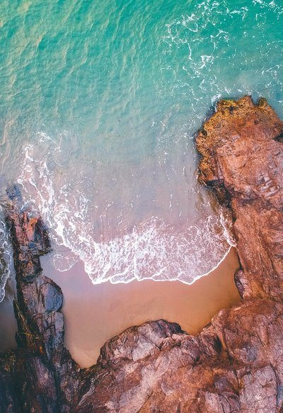 Aerial View Of Sea Rolling Into A Rocky Shore