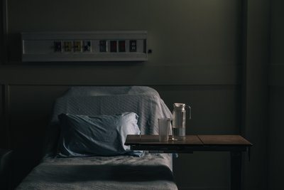 An Empty Hospital Bed In A Darkening Room