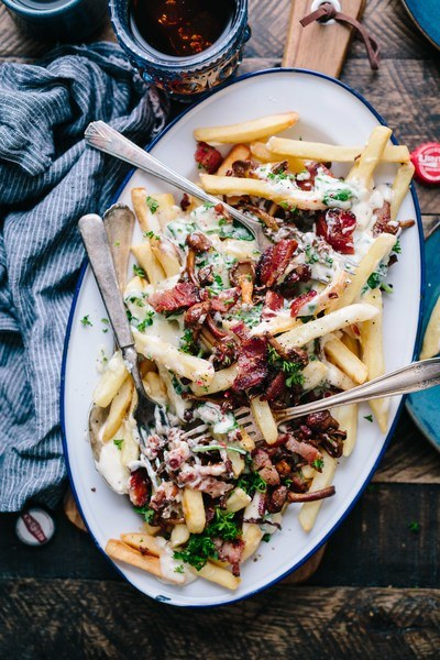 Bacon Strips And Melted Cheese Topped Fries on Oval White And