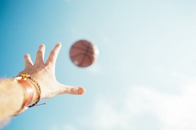 Basketball und Hand in Sky