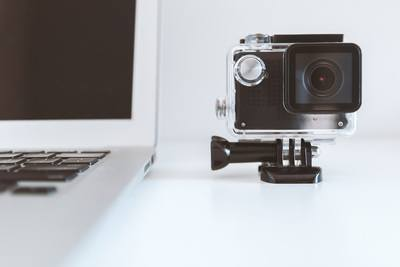 Black Action Camera Beside White Laptop