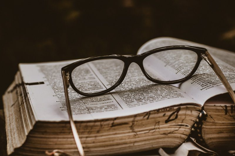 Black Spectacles Otop An Open Book