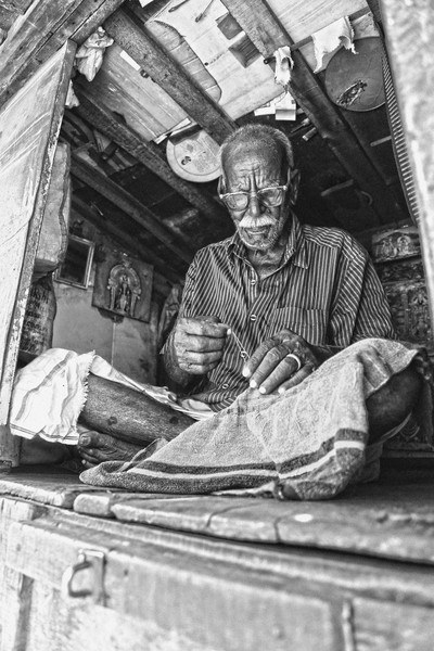 Black & White  Man Sewing Textile While Sitting on Floor