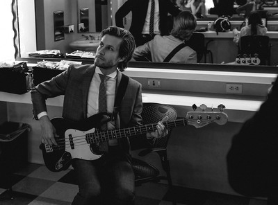 Black & White Photography of Man Wearing Suit Holding Guitar