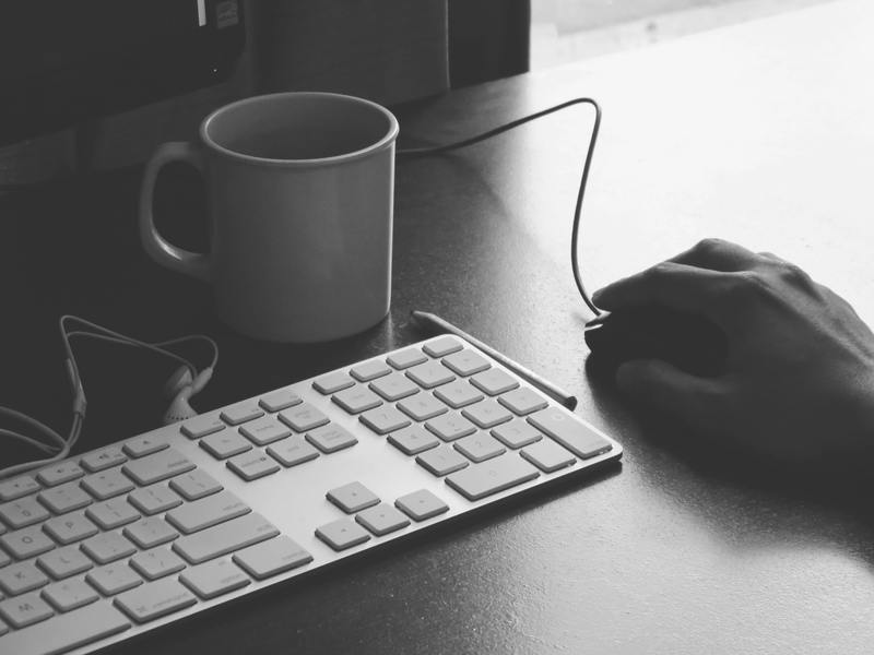 Black & White Photography of Person Holding Computer Mouse Near Keyboard And Mug