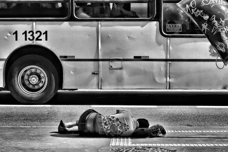 Black & White Photography of Person Laying on Ground Near Bus