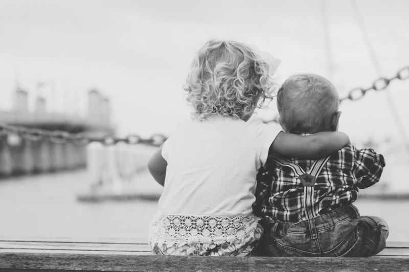 Black & White Photography of Two Children Sitting on Ledge