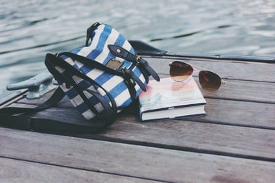 Blue And White Striped Crossbody Bag Near Book And Sunglasses on