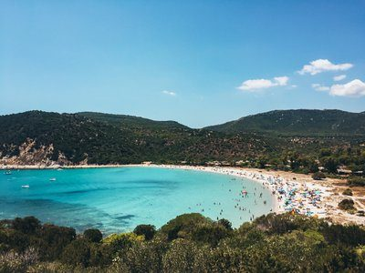 Blue Water Bay With Busy Beach