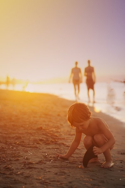 Boy Playing Sand on Seashore at Sunset