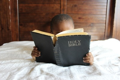 Boy Reading Holy Bible While Lying on Bed